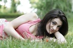 La fille détendent sur l'herbe Photographie stock