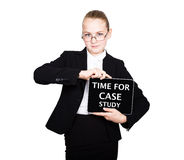 La fille d'école dans un costume tient un comprimé de PC dans des ses mains avec l'inscription - heure pour l'étude de cas photographie stock