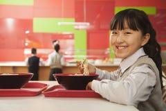 La fille d'école mange des nouilles dans la cafétéria de l'école Photo libre de droits