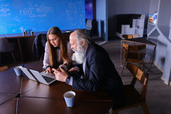 La fille d'étudiant explique comment utiliser l'ordinateur portable au professeur, donnent advic Photos libres de droits