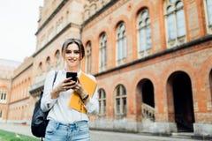 La fille d'étudiant a lu quelque chose sur le smartphone extérieur dans le campus image stock