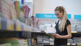 La fille d'étudiant renverse des pages de carnet dans une boutique de papeterie banque de vidéos