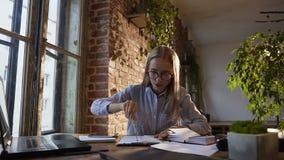 La fille d'étudiant travaille dans un bureau moderne avec une grande fenêtre et un mur de briques rouge, concentre et dessine des clips vidéos