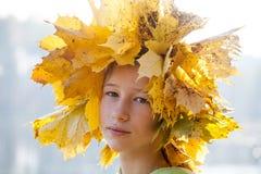 La fille d'adolescent dans des feuilles jaunes d'érable tressent photographie stock