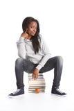 La fille d'adolescent noire d'étudiant s'assied sur des livres d'éducation Photos stock