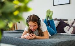 La fille d'adolescent ont l'amusement avec la pose mobile sur le lit écoutant la musique d'un smartphone Photographie stock