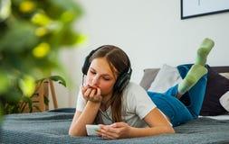 La fille d'adolescent ont l'amusement avec la pose mobile sur le lit écoutant la musique d'un smartphone Photo stock