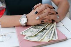 La fille d'affaires dans un restaurant s'assied à une table avec un mone de comprimé photographie stock