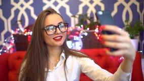 La fille d'affaires fait à selfie le téléphone Un étudiant aux cheveux longs mignon ayant l'amusement dans un café Le concept de  clips vidéos