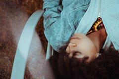 La fille d'Afro slieeping sur la chaise de plate-forme extérieure photos libres de droits