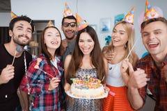La fille d'anniversaire tient un gâteau avec des bougies Les filles et les types se tiennent autour de elle Photo stock