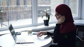 La fille d'Attarctive avec le hijab arabe traditionnel travaille à quelque chose sur son ordinateur portable et puis met des écou banque de vidéos