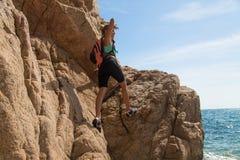 La fille d'aventure s'élève sur une falaise, riches la cible Photographie stock libre de droits