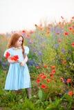 La fille d'or d'enfant recueille un bouquet des fleurs sauvages pour la mère Photo stock