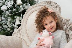 La fille d'enfant avec le jouet de moutons s'assied près de l'arbre de Noël image libre de droits