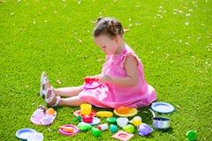 La fille d'enfant d'enfant en bas âge jouant avec la nourriture joue se reposer dans le gazon Image stock