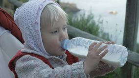 La fille d'enfant dans le hoodie et le gilet tricoté rouge boit la boisson de lait ou de laiterie de la bouteille en plastique si banque de vidéos