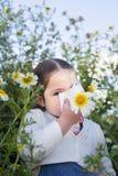La fille d'enfant en bas âge éternuant dans une marguerite fleurit Photo stock