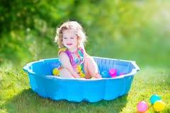 La fille d'enfant en bas âge jouant des boules dans le jardin Photographie stock libre de droits