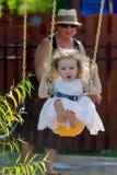 La fille d'enfant en bas âge sur l'oscillation a poussé par sa grand-mère Image libre de droits