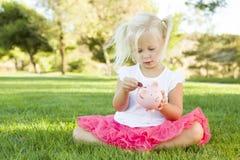 La fille d'enfant en bas âge met une pièce de monnaie à sa tirelire dehors Photos stock