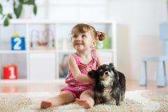 La fille d'enfant et son chien jouent dans la crèche Photos libres de droits