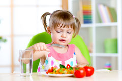La fille d'enfant mange les légumes frais Consommation saine pour Images stock