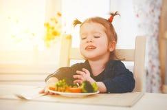 La fille d'enfant n'aime pas et ne veut pas manger des légumes photos stock