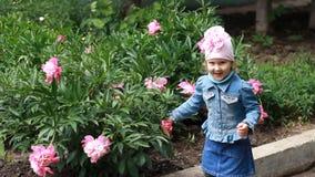 La fille d'enfant renifle l'arome des fleurs de pivoine et éternue Allergies du ` s d'enfants clips vidéos