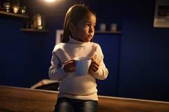 La fille d'enfant s'assied illuminé par l'ampoule avec une tasse de thé dans h images stock
