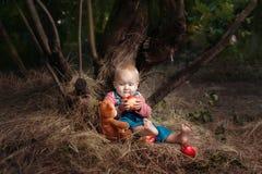 La fille d'enfant s'assied sous un arbre image stock