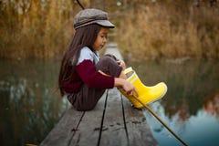 La fille d'enfant s'assied sur le pont de pêche en bois et pêche des poissons avec s photographie stock