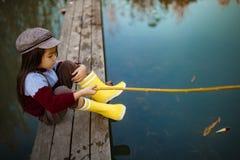 La fille d'enfant s'assied sur le pont de pêche en bois et pêche des poissons avec s image stock