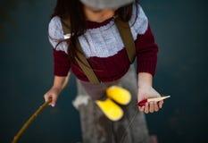 La fille d'enfant se tient dans des ses mains canne à pêche qui a réussi tout seul et flotteur images stock