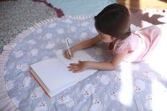 La fille d'enfant se trouve sur le tapis et dessine photographie stock