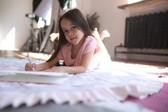 La fille d'enfant se trouve sur le tapis et dessine photos libres de droits