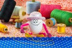 La fille d'oeuf de pâques dans un chapeau drôle est occupée à coudre Photos stock