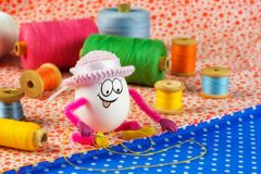 La fille d'oeuf de pâques dans un chapeau est occupée à coudre Images libres de droits