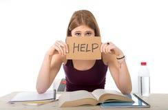 La fille d'étudiant universitaire étudiant pour l'examen d'université s'est inquiétée dans l'effort demandant l'aide Image stock