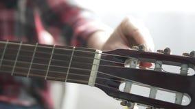 La fille dans la chemise de plaid accorde la guitare