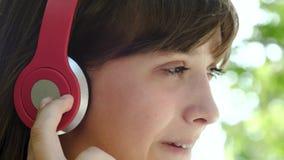 La fille dans des écouteurs boit le cocktail frais du tube, appréciant la musique des haut-parleurs, les rires et les sourires Pl clips vidéos