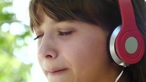 La fille dans des écouteurs boit le cocktail frais du tube appréciant la musique des haut-parleurs, des rires et des sourires Pla banque de vidéos