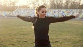 La fille dans des écouteurs exécute des exercices de forme physique pendant le matin d'automne clips vidéos