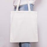 La fille dans des blues-jean tient le sac d'emballage vide d'eco de coton, maquette de conception Panier fait main pour des fille Photographie stock