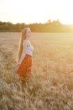 La fille dans des bras debout de champ de blé tendus au coucher du soleil et apprécient l'extérieur, vue de côté Photos libres de droits