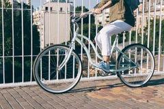 La fille dans des jeans veste et espadrilles monte le pont sur un bicycl Photos libres de droits