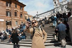 La fille dans des lunettes de soleil fait le selfie sur des escaliers avec le fond de personnes à la place de l'Espagne à la capi photo libre de droits