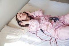 La fille dans des pyjamas roses se trouvant sur le lit et écoute la musique avec des écouteurs photo libre de droits