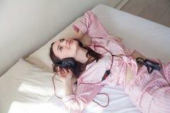 La fille dans des pyjamas roses se trouvant sur le lit et écoute la musique avec des écouteurs photographie stock libre de droits