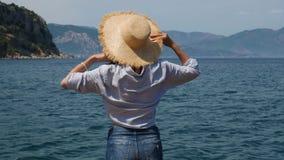 La fille dans des shorts d'une chemise bleue et de denim se tient prêt la mer dans un chapeau de paille banque de vidéos
